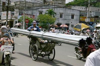 自転車でパイプを運搬